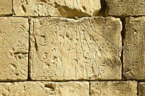 relojes antiguos de Sol sobre un muro de piedra